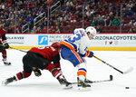New York Islanders center Mathew Barzal (13) shields the puck from Arizona Coyotes defenseman Jakob Chychrun in the first period during an NHL hockey game, Monday, Feb. 17, 2020, in Glendale, Ariz. (AP Photo/Rick Scuteri)