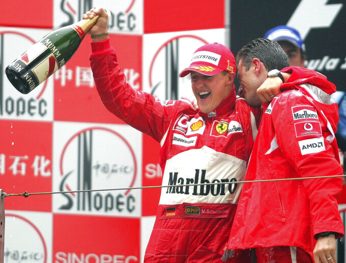 FILE - In this Sunday Oct. 1, 2006 file photo, Germany's Michael Schumacher, left, celebrates his win in the Formula One Chinese Grand Prix with race engineer Chris Dyer, at the Shanghai International Circuit in Shanghai, China. British driver Lewis Hamilton made Formula One history on Sunday, Oct. 25, 2020 winning the Portuguese Grand Prix for a 92nd win to move one ahead of German great Michael Schumacher. (AP Photo/Greg Baker, file)