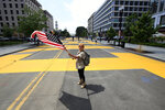 Beth Shafa waves an American Flag near the White House, Friday, June 5, 2020, in Washington. City workers and activists painted the words Black Lives Matter in enormous bright yellow letters on the street leading to the White House, a highly visible sign of the District of Columbia's embrace of a protest movement that has put it at odds with President Donald Trump. (AP Photo/Manuel Balce Ceneta)
