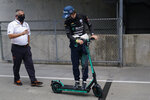 Gil de Ferran, left, talks with Fernando Alonso, of Spain, as the go back to the garage during a practice session for the Indianapolis 500 auto race at Indianapolis Motor Speedway, Thursday, Aug. 13, 2020, in Indianapolis. (AP Photo/Darron Cummings)