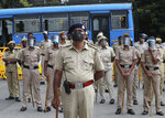 Indian police officials wearing face shields and masks as a precaution against the coronavirus stand guard during a protest against a pair of controversial agriculture bills in Bengaluru, India, Monday, Sept. 28, 2020. India's confirmed coronavirus tally has reached 6 million cases, keeping the country second to the United States in number of reported cases since the pandemic began. (AP Photo/Aijaz Rahi)
