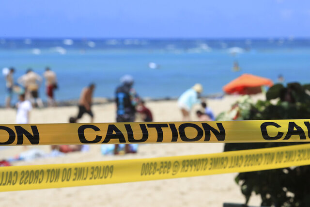 FILE - In this Friday, March 20, 2020, file photo, as beachgoers are seen in the background, yellow caution tape wrapped across Waikiki in Honolulu. Hawaii's governor has instituted a mandatory 14-day self quarantine starting Thursday, March 27, of all people traveling to the state as part of efforts to fight the spread of coronavirus. The order applies toreturning residents, as well as visitors. (AP Photo/Marco Garcia, File)