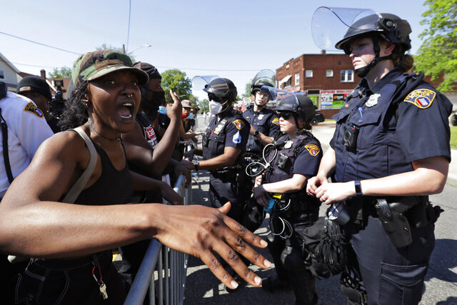 FILE - In this June 2, 2020 file photo, a protester voices her concerns to a Cleveland police officer during a rally for black lives in Cleveland.  Ohio would create the first statewide disciplinary database for violent officers and require law enforcement to undergo psychological testing under a proposal unveiled Thursday, June 11,  by House Republicans. The legislation comes as the state grapples with the aftermath of civil unrest over the killing of George Floyd in Minneapolis. (AP Photo/Tony Dejak, File)