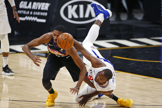 Phoenix Suns forward Mikal Bridges, left, loses the ball as he is fouled by Los Angeles Clippers forward Serge Ibaka (9) during the first half of an NBA basketball game Sunday, Jan. 3, 2021, in Phoenix. (AP Photo/Ralph Freso)