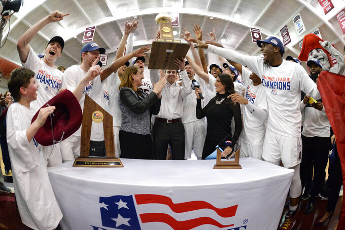 Colgate coach Matt Langel, center, lifts the trophy after the team's NCAA college basketball game against Bucknell for the championship of the Patriot League men's tournament in Hamilton, N.Y., Wednesday, March 13, 2019. Colgate won 94-80. (AP Photo/Adrian Kraus)