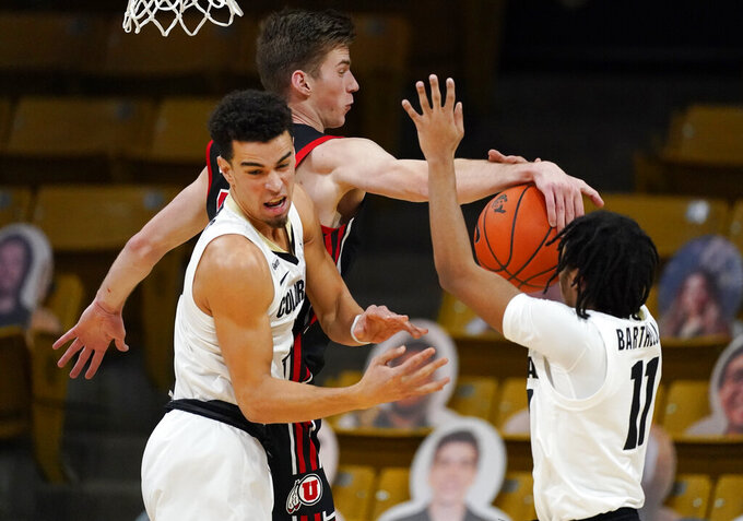 Utah center Branden Carlson, back left, blocks a shot by Colorado guard Keeshawn Barthelemy, right, as Colorado guard Maddox Daniels, front left, tries to clear out of the way in the second half of an NCAA college basketball game Saturday, Jan. 30, 2021, in Boulder, Colo. (AP Photo/David Zalubowski)