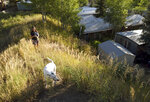 ADVANCE ON THURSDAY, SEPT. 12 FOR USE ANY TIME AFTER 3:01 A.M. SUNDAY SEPT 15 - Pitkin County Commissioner Patti Kay-Clapper walks with her dog near her home at the Smuggler Trailer Court outside Aspen, Colo., on Tuesday, Aug. 27, 2019. Clapper says that in the early 1980s, the county allowed Smuggler residents to own their homes and their lots in an effort to keep the community affordable. She now is trying to preserve the county's remaining mobile home parks as affordable housing. (AP Photo/Thomas Peipert)