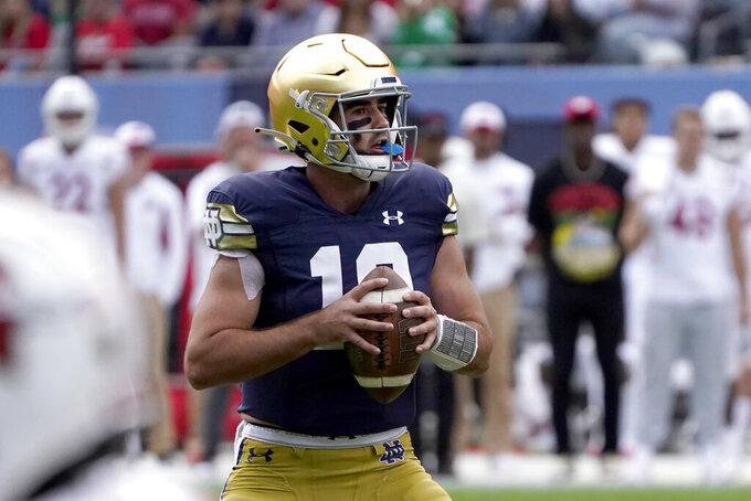 Notre Dame quarterback Drew Pyne looks downfield before showing a touchdown pass to wide receiver Kevin Austin Jr., during the second half of an NCAA college football game Saturday, Sept. 25, 2021, in Chicago. Notre Dame won 41-13. (AP Photo/Charles Rex Arbogast)