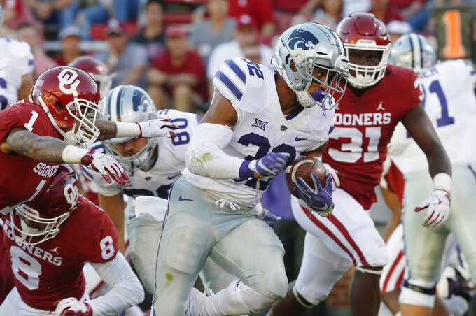Kansas State running back Justin Silmon carries past Oklahoma cornerback Jordan Parker (1) and defensive end Jalen Redmond (31) for a touchdown in the second half of an NCAA college football game in Norman, Okla., Saturday, Oct. 27, 2018. (AP Photo/Sue Ogrocki)
