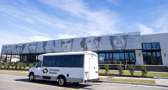 A legacy shuttle drives by the EJI Legacy Pavilion, that features the faces of Civil Rights warriors, in Montgomery, Ala., on Friday January 17, 2020. The Pavilion, which houses the EJI ticket office, a gift shop, a restaurant, a coffee shop, civil rights displays and a shuttle stop for the Legacy Museum and the Peace and Justice Memorial opens on Saturday January 18, 2020. (Mickey Welsh/Montgomery Advertiser via AP)