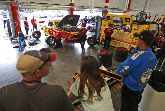 Fans watch the team of Joey Logano as they work on the car in the garage at Richmond International Raceway in Richmond, Va., Friday, April 12, 2019. (AP Photo/Steve Helber)