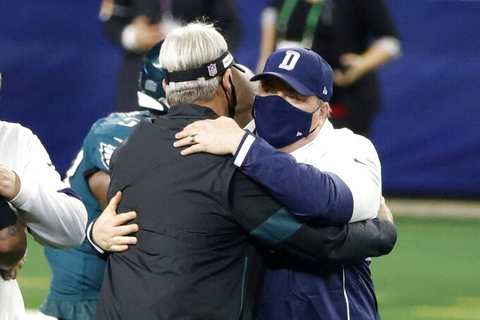 Philadelphia Eagles head coach Doug Pederson, left, and Dallas Cowboys head coach Mike McCarthy greet each other after their NFL football game in Arlington, Texas, Sunday, Dec. 27. 2020. (AP Photo/Michael Ainsworth)