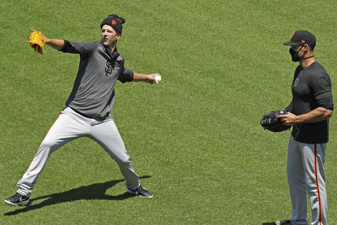 San Francisco Giants' manager Gabe Kapler, right, watches pitcher Drew Smyly pitch during a baseball practice on Friday, July 3, 2020, in San Francisco. (AP Photo/Ben Margot)