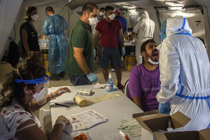 FILE - Medical staff of the National Health Organization (EODY) conduct tests for the new coronavirus from migrants in Moria refugee camp on the northeastern Aegean island of Lesbos, Greece, on Friday, Sept. 4, 2020. A major testing and contact-tracing operation at Greece's largest migrant camp on the eastern island of Lesbos has so far detected 17 confirmed cases of COVID-19 infection among the 12,500 people living in the overcrowded facility, officials said on Tuesday, Sept. 8, 2020. (AP Photo/Panagiotis Balaskas, File)