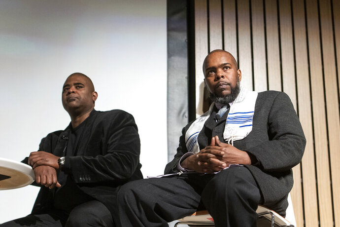 Anthony Wilson, left, and Jeffrey Wilson, brothers of Ben Wilson, who was murdered in 1984, speaks with William Moore, former U.S. Secretary of Education Arne Duncan and Rapper Common at Malcom X College, during a conversation and private screening of