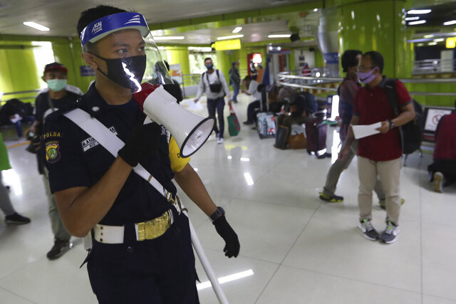 A security guard wearing protective gears uses a megaphone to give directions to arriving train passengers to have their travel documents checked at Gambir Station during the large-scale restrictions imposed to curb the spread of the new coronavirus outbreak in Jakarta, Indonesia Thursday, May 28, 2020. (AP Photo/Achmad Ibrahim)