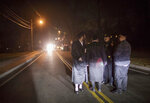 Orthodox Jewish talk to stand on Forshay Road in Monsey, N.Y., Sunday, Dec. 29, 2019, down the street from the scene of a stabbing that occurred late Saturday during a Hanukkah celebration. A man attacked at a rabbi's home north of New York City late Saturday, stabbing and wounding several people before fleeing in a vehicle, police said. (AP Photo/Allyse Pulliam)