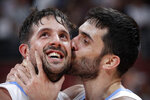 Facundo Campazzo of Argentina, right, kisses teammate Nicolas Laprovittola as they celebrate after beating France in their semifinal match against in the FIBA Basketball World Cup at the Cadillac Arena in Beijing, Friday, Sept. 13, 2019. (AP Photo/Mark Schiefelbein)