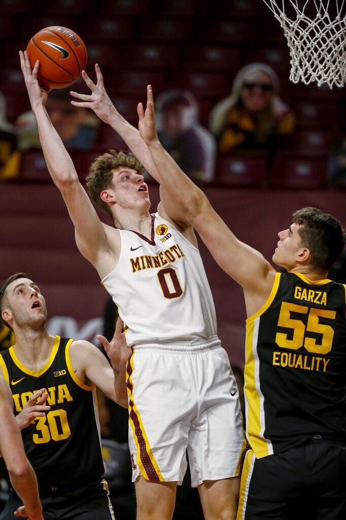 Minnesota center Liam Robbins (0) shoots against Iowa center Luka Garza (55) during the first half of an NCAA college basketball game Friday, Dec. 25, 2020, in Minneapolis. (AP Photo/Bruce Kluckhohn)