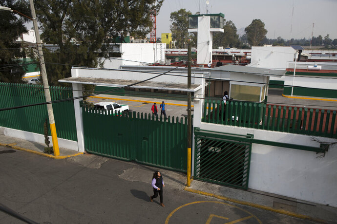 FILE - In this Dec. 31, 2015 file photo, a woman walks past Las Agujas immigration detention center in Mexico City. Mexico's National Human Rights Commission said on Friday, July 19, 2019, that the migrant detention center in the capital suffers from bedbugs, bad food and overcrowding. The governmental commission said the issues were pointed out more than a year ago and still haven't been resolved. (AP Photo/Rebecca Blackwell, File)