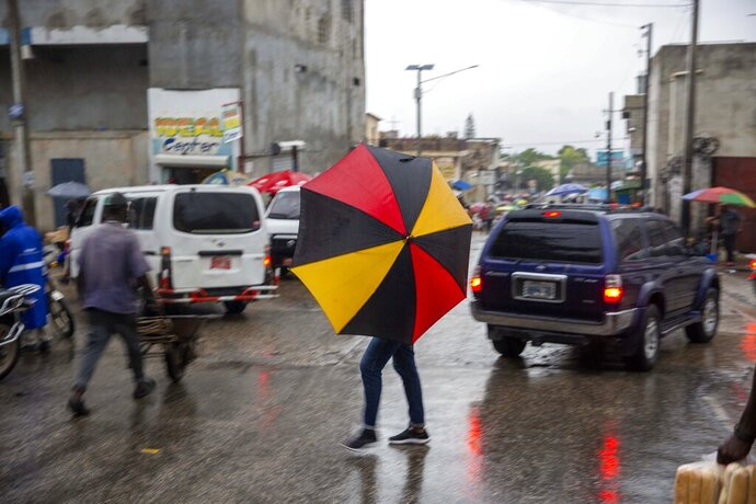 Pedestrians venture out into the rain brought by the outer bands of Hurricane Isaias in the Petionville district of Port-au-Prince, Haiti, early Friday, July 31, 2020. Isaias kept on a path early Friday toward the U.S. East Coast as it approached the Bahamas. (AP Photo/Dieu Nalio Chery)