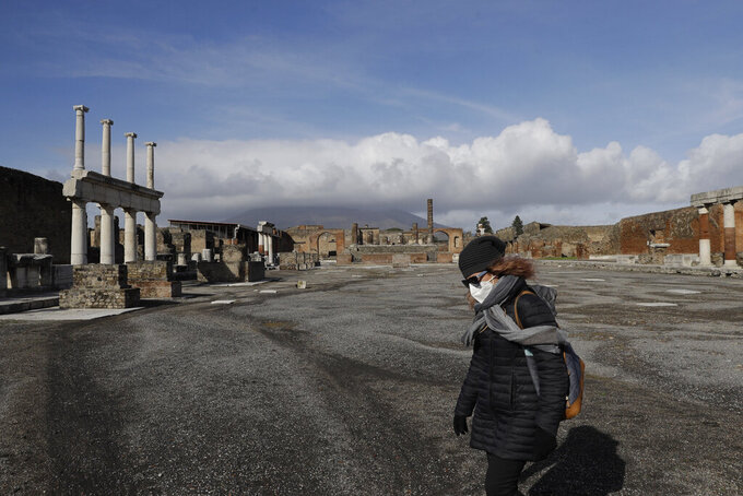 Clouds hang over the Vesuvius volcano, background, as a woman walks in the Forum of the archeological site of Pompeii, southern Italy, during the inauguration of the museum Antiquarium, Monday, Jan. 25, 2021. Decades after suffering bombing and earthquake damage, Pompeii's museum is back in business, showing off exquisite finds from excavations of the ancient Roman city. Officials of the archaeological park of the ruins of the city destroyed in 79 A.D. by the eruption of Mount Vesuvius inaugurated the museum on Monday. (AP Photo/Gregorio Borgia)