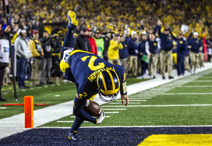 Michigan quarterback Shea Patterson scores a touchdown during the third quarter of an NCAA college football game against Wisconsin in Ann Arbor, Mich., Saturday, Oct. 13, 2018. Michigan won 38-13. (AP Photo/Tony Ding)