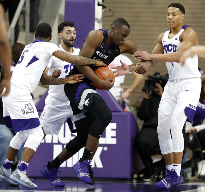 TCU guard Kendric Davis (5), Alex Robinson, rear, and Desmond Bane, right, work to strip the ball away from Kansas State forward Makol Mawien, center, in the second half of an NCAA college basketball game in Fort Worth, Texas, Monday, March 4, 2019. (AP Photo/Tony Gutierrez)