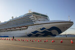 FILE - In this Feb. 11, 2020, file photo, a reporter walks near the quarantined Diamond Princess cruise ship in Yokohama, near Tokyo. Life on board the luxury cruise ship, which has dozens of cases of a new virus, can include fear, excitement and soul-crushing boredom, according to interviews by The Associated Press with passengers and a stream of tweets and YouTube videos.  (AP Photo/Jae C. Hong, File)