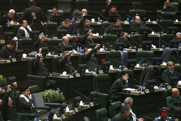 Wearing the uniform of the Iranian Revolutionary Guard, lawmakers chant slogan during an open session of parliament in Tehran, Iran, Tuesday, April 9, 2019. Chanting