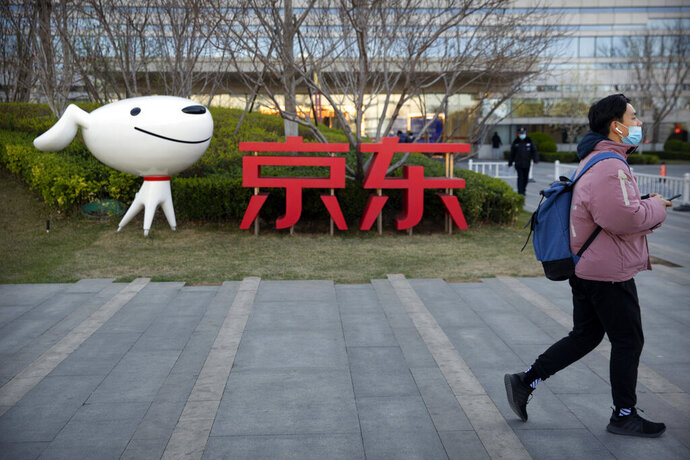 FILE - In this March 27, 2020, file photo, a man walks past the JD.com logo outside the company's headquarters in Beijing. China's market regulator on Thursday, Dec. 31, 2020, fined JD.com Inc., a unit of Alibaba Group and a third e-commerce outlet on charges of misreporting prices and other offenses amid a campaign to tighten official control over the booming industry. (AP Photo/Mark Schiefelbein, File)