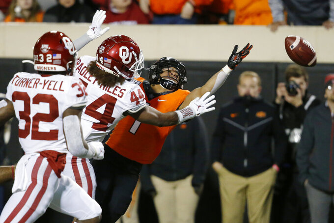 Oklahoma State wide receiver Landon Wolf (1) can't reach the ball on a pass in front of Oklahoma safety Delarrin Turner-Yell (32) and Brendan Radley-Hiles (44) in the second half of an NCAA college football game in Stillwater, Okla., Saturday, Nov. 30, 2019. (AP Photo/Sue Ogrocki)
