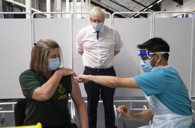 Britain's Prime Minister Boris Johnson watches first responder Caroline Cook receiving an injection of a Covid-19 vaccine at Ashton Gate Stadium in Bristol, England, Monday Jan. 11, 2021. The center is one of the seven mass vaccination centers now opened to the general public as the government continues to ramp up the vaccination programme against Covid-19. (Eddie Mulholland/Pool via AP)