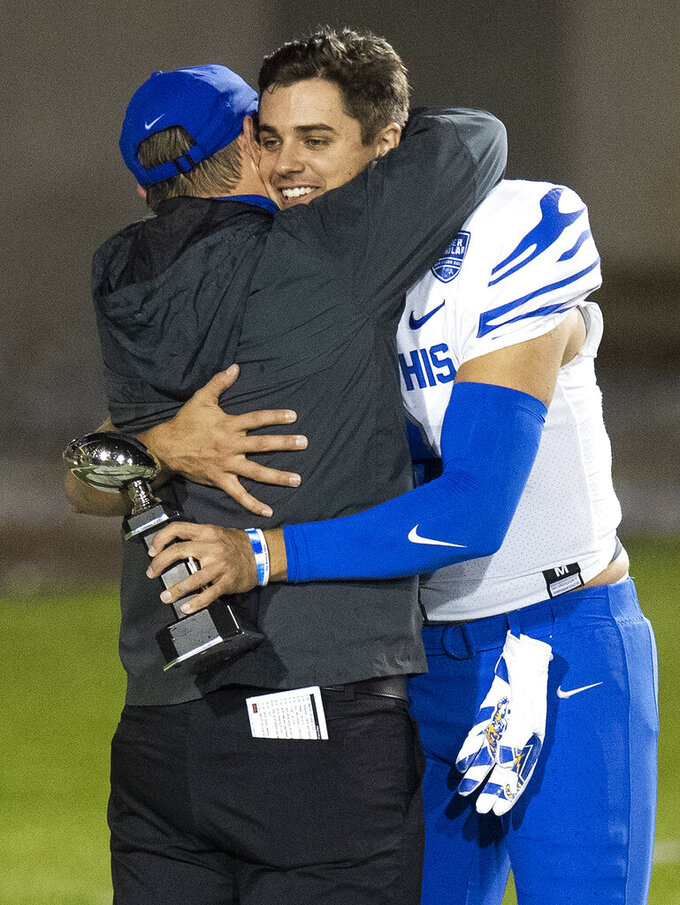 Memphis quarterback Brady White (3) holds his MVP trophy as he hugs Memphis head coach Ryan Silverfield after the team defeated Florida Atlantic in the Montgomery Bowl NCAA college football game, Wednesday, Dec. 23, 2020, in Montgomery, Ala. (Mickey Welsh/The Montgomery Advertiser via AP)