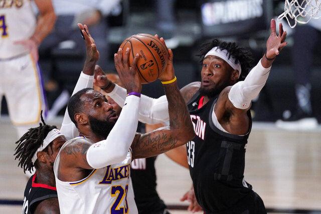 Los Angeles Lakers' LeBron James (23) drives to the basket past Houston Rockets' Robert Covington (33) during the first half of an NBA conference semifinal playoff basketball game Tuesday, Sept. 8, 2020, in Lake Buena Vista, Fla. (AP Photo/Mark J. Terrill)