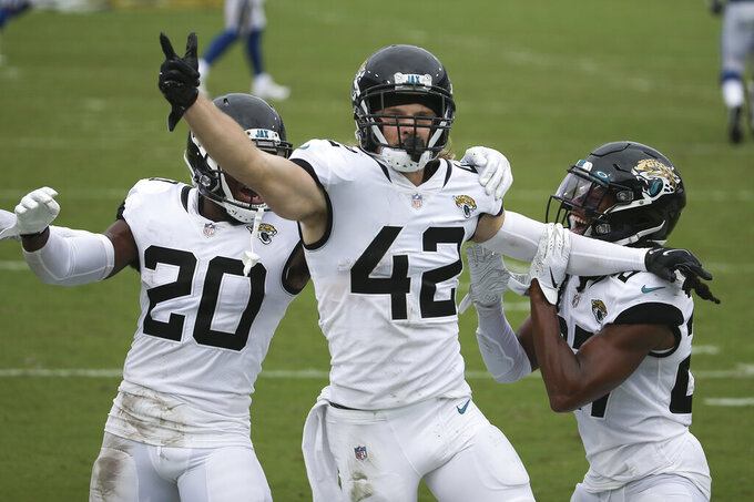 Jacksonville Jaguars safety Andrew Wingard (42) celebrates after intercepting a Indianapolis Colts pass with teammates safety Daniel Thomas (20) and Chris Chaisson, right, during the second half of an NFL football game, Sunday, Sept. 13, 2020, in Jacksonville, Fla. (AP Photo/Stephen B. Morton)