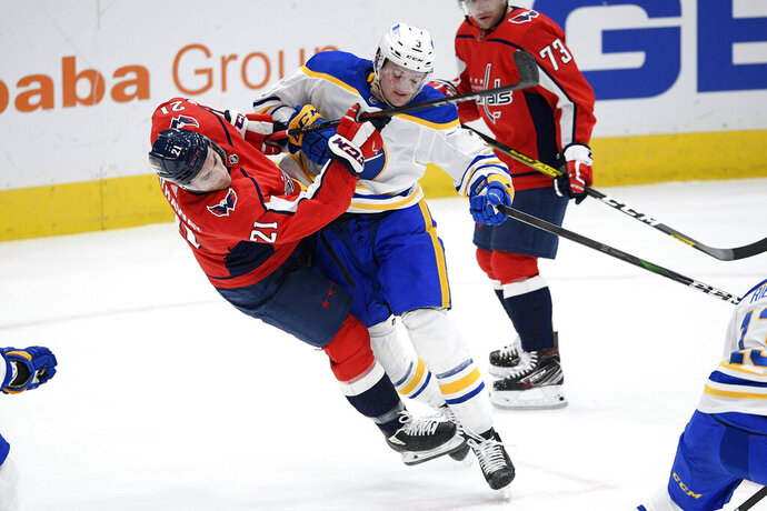 Buffalo Sabres defenseman William Borgen (3) shoves Washington Capitals right wing Garnet Hathaway (21) during the second period of an NHL hockey game Thursday, Feb. 18, 2021, in Washington. (AP Photo/Nick Wass)