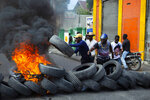 Protesters throw wheels onto a burning barricade during a demonstration demanding the resignation of President Jovenel Moise, in Port-au-Prince, Haiti, Friday, Jan. 15, 2021. Moise has one more year in power, but a growing groundswell of opposition is organizing protests and demanding he resign next month amid spiraling crime, a crumbling economy and approval of what critics say are illegal presidential decrees and unconstitutional moves, worrying many that Moise is amassing too much power as he enters his second year of rule by decree. (AP Photo/Joseph Odelyn)