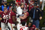 Players celebrate with Alabama head coach Nick Saban after their win against Ohio State in an NCAA College Football Playoff national championship game, Monday, Jan. 11, 2021, in Miami Gardens, Fla. Alabama won 52-24. (AP Photo/Wilfredo Lee)