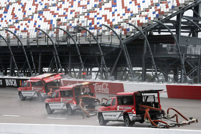 A crew tries to dry off the track after a rain before the Toyota 500 NASCAR Cup Series auto race Wednesday, May 20, 2020, in Darlington, Tenn. (AP Photo/Brynn Anderson)