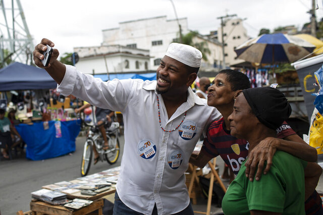 "Wagner Luiz Abreu Machado, a priest from the Afro-Brazilian faith Umbanda who goes by Waguinho Macumba, takes a selfie with residents as he campaigns for a seat on the Sao Goncalo City Council with the Brazilian Social Democracy Party (PSDB) in Sao Goncalo, Rio de Janeiro state, Brazil, Sunday, Nov. 8, 2020. ""No city councilor is committed to our causes,"" Machado said, referring to the followers of African-influenced faiths. (AP Photo/Bruna Prado)"