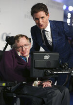 FILE - In this Tuesday, Dec. 9, 2014 file photo actor Eddie Redmayne, right, and Professor Stephen Hawking arrive on the blue carpet for the UK premiere of The Theory Of Everything at the Odeon in Leicester Square, central London. Hawking, whose brilliant mind ranged across time and space though his body was paralyzed by disease, has died, a family spokesman said early Wednesday, March 14, 2018. (Photo by Joel Ryan/Invision/AP, File)
