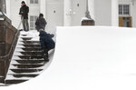 Men take pictures of the snow sweeping across the steps before Helsinki Cathedral during a heavy snow storm making all kinds of travel difficult in Helsinki, Finland, on Tuesday Jan. 12, 2021. The heavy snowfall is predicted to continue until Wednesday in Southern Finland. (Vesa Moilanen/Lehtikuva via AP)