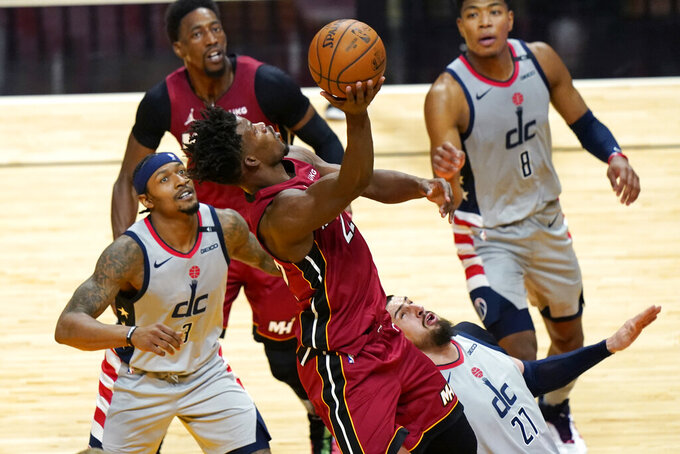 Miami Heat forward Jimmy Butler, center, goes to the basket as Washington Wizards guard Bradley Beal (3) and center Alex Len (27) defend during the second half of an NBA basketball game, Wednesday, Feb. 3, 2021, in Miami. (AP Photo/Lynne Sladky)