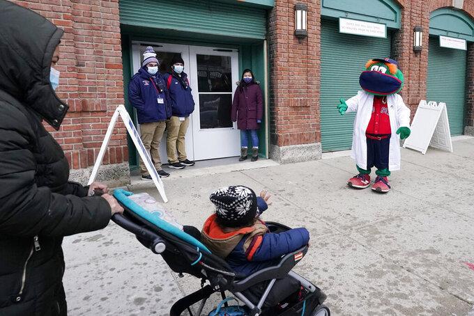 A child waves to Boston Red Sox mascot, Wally the Green Monster, dressed in a medical white coat outside Fenway Park, Monday Feb. 1, 2021, in Boston. Fenway Park is one of several large COVID-19 vaccination sites in the Boston area. (AP Photo/Elise Amendola)