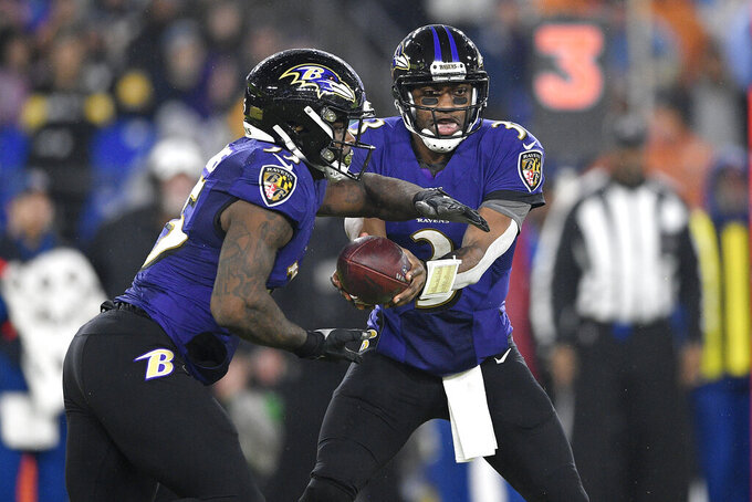 Baltimore Ravens quarterback Robert Griffin III, right, hands off to running back Gus Edwards during the first half of an NFL football game against the Pittsburgh Steelers, Sunday, Dec. 29, 2019, in Baltimore. On the run, the Ravens set a new NFL record for yards rushing in a season by a team. Baltimore entered its game against Pittsburgh needing 93 yards to eclipse the 3,165 yards that New England amassed on the ground in 1978. (AP Photo/Nick Wass)