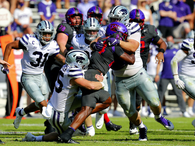 TCU running back Darwin Barlow (24) is hit by Kansas State linebacker Cody Fletcher (55) and defensive tackle Drew Wiley (59) in the first quarter of an NCAA college football game Saturday, Oct. 10, 2020, in Arlington, Texas. (AP Photo/Richard W. Rodriguez)