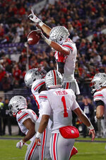 Ohio State wide receiver Austin Mack is lifted after scoring on a pass from quarterback Justin Fields during the second half of the team's NCAA college football game against Northwestern on Friday, Oct. 18, 2019, in Evanston, Ill. Ohio State won 52-3. (AP Photo/Charles Rex Arbogast)