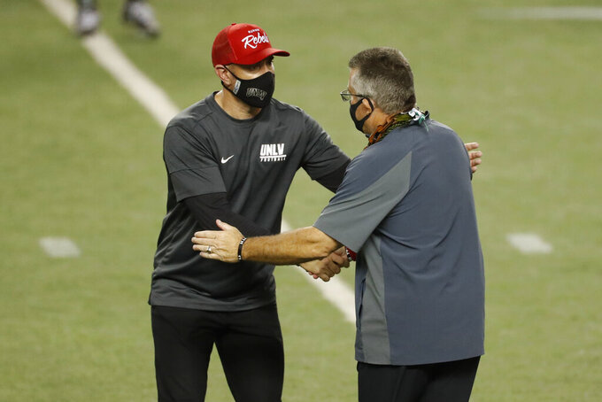 UNLV head coach Marcus Arroyo, left, shakes hands with Hawaii head coach Todd Graham at the end of an NCAA college football game Saturday, Dec. 12, 2020, in Honolulu. Hawaii defeated UNLV 38-21. (AP Photo/Marco Garcia)