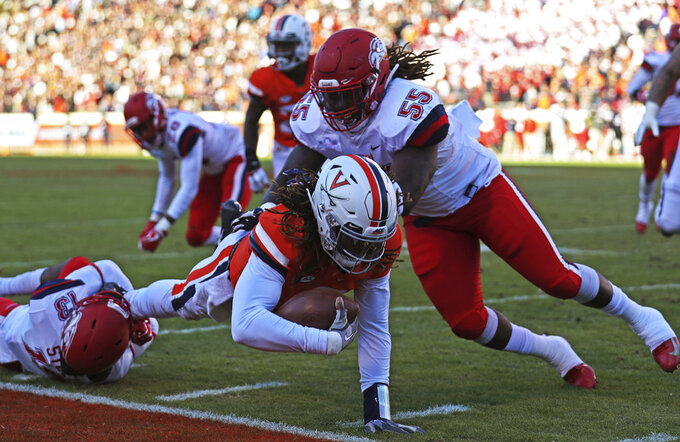 Virginia's quarterback Bryce Perkins (3) is tackled by two Liberty defenders in the first half  of an NCAA college football game against Saturday, Nov. 10, 2018, in Charlottesville, Va. (Zack Wajsgras /The Daily Progress via AP)